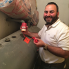 Greg Hovagim, Tank Clarity Co-founder, installing a Tank Clarity sensor on an oil tank